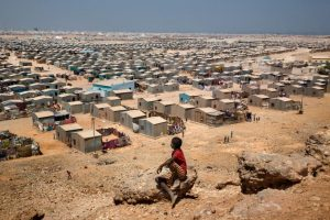 Africa, Somalia, Bosaso. 05/10/2015. Bosaso: the coastal city of 700,000 inhabitants. It is the main port of Somalia and it is the capital of Puntland; this macro-northern region, compare to the rest of the country, enjoys of a relative political and military stability. A kid look at the Buulo Mingis Settlement IDP camp.